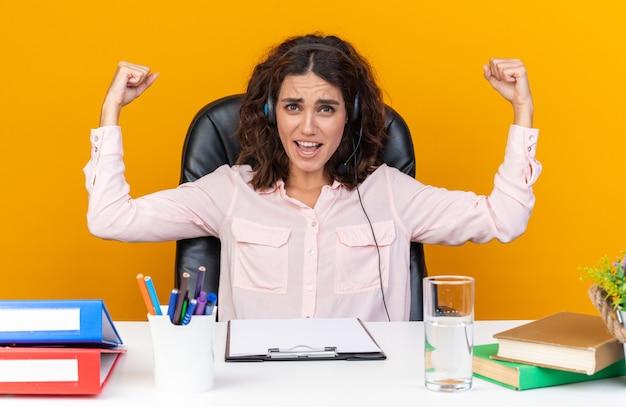 Operatore di call center femminile abbastanza caucasico felice sulle cuffie seduto alla scrivania con strumenti da ufficio che tende i suoi bicipiti isolati sul muro arancione
