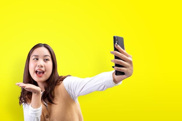 Felice bella ragazza fa autoritratto sullo smartphone su sfondo giallo.