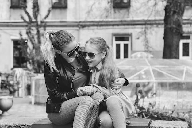 Felice bella madre e piccola sua figlia carina in abiti casual in panchina vicino a casa in cortile. concetto di trascorrere del tempo insieme ai bambini e alle relazioni adorabili della famiglia. copia spazio per il sito