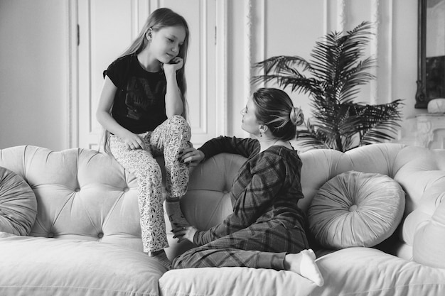 Felice bella madre e piccola sua figlia carina in abiti casual in soggiorno sul divano. concetto di trascorrere del tempo insieme ai bambini e alle relazioni adorabili della famiglia. copia spazio per il sito