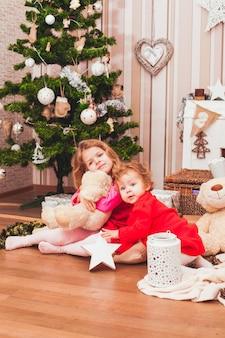 Sorelle graziose felici che si siedono nella stanza decorata di natale