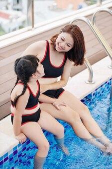 Felice bella donna vietnamita e la sua piccola figlia seduti sul bordo della piscina e discutendo le vacanze estive