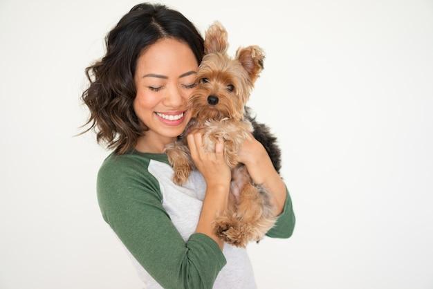 Donna graziosa felice che abbraccia yorkshire terrier