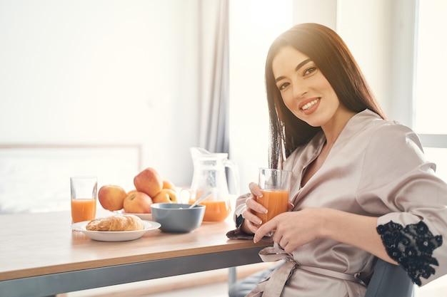 Felice bella donna seduta a tavola con un sorriso solare e gustando cibi leggeri per colazione
