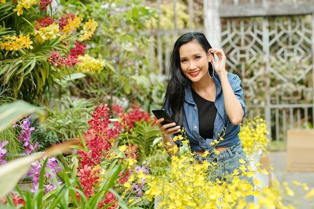 Felice bella giovane donna asiatica che fotografa piante in fiore in un vivaio di fiori e sorride alla telecamera