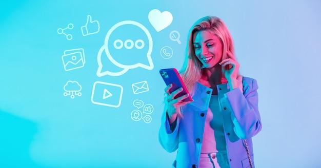 Ragazza alla moda abbastanza giovane felice che tiene un telefono cellulare e comunica nei social network con le icone. concetto di comunicazione internet