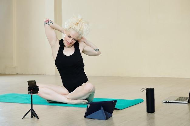 Felice ballerina in forma piuttosto giovane che fa esercizi di stretching e spiega ogni dettaglio agli studenti durante le lezioni online