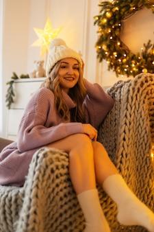 Felice bella ragazza con il sorriso in un maglione lavorato a maglia vintage con calzini e un cappello si siede e riposa su una sedia con una coperta di lana vicino alle decorazioni natalizie e alle luci a casa.
