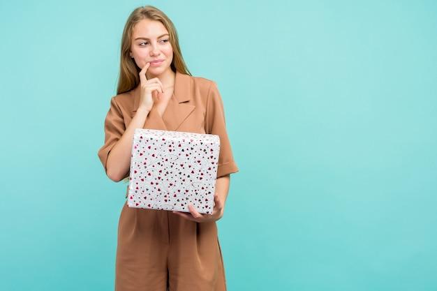 Felice piuttosto giovane donna azienda confezione regalo su sfondo blu.