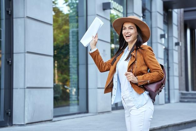 Felice bella giovane donna con zaino agitando la mano in città. concetto di stile di vita