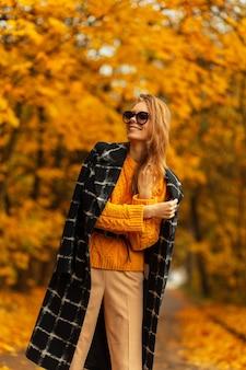 Felice bella giovane donna con un bel sorriso con occhiali da sole in cappotto nero alla moda con maglione giallo vintage che si gode il clima autunnale all'aperto con fogliame giallo colorato