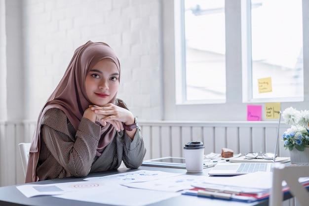 Hijab marrone professionale felice della donna di affari araba che lavora a casa.