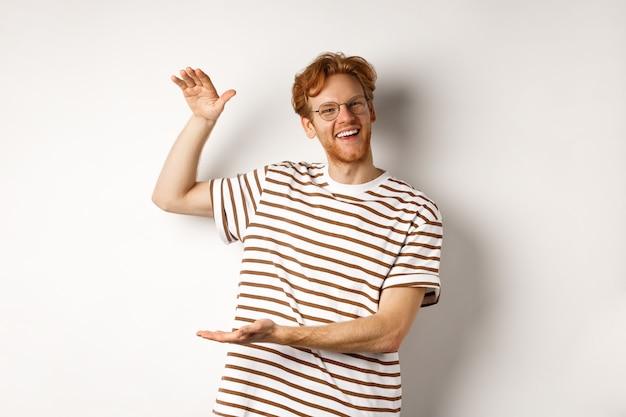 Ragazzo rosso felice e orgoglioso con gli occhiali che mostrano qualcosa di grande, modellando un oggetto di grandi dimensioni con le mani su sfondo bianco, sorridendo alla telecamera.