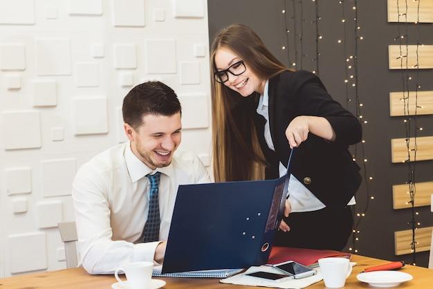 Felice orgogliosa coppia di affari di successo che sorride con la cartella, guardando qualcosa