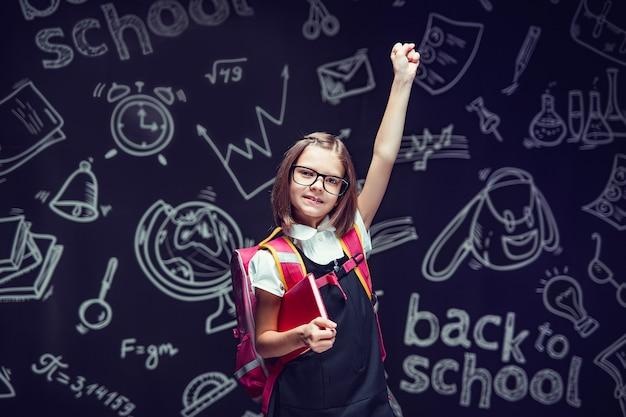 Allievo felice con gli occhiali che si prepara per andare a scuola con in mano il libro alzando la mano per tornare a scuola