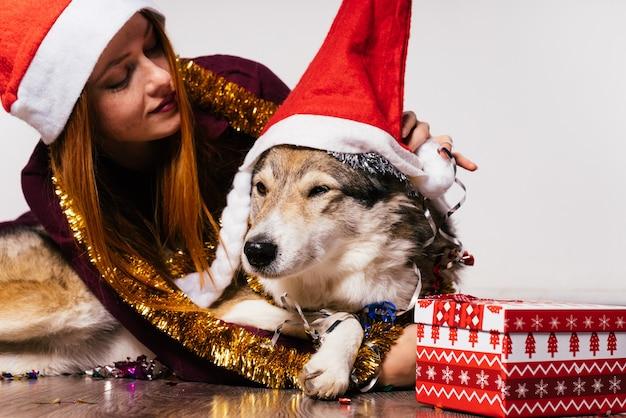 Felice ragazza dai capelli rossi con un berretto rosso come babbo natale si siede sul pavimento con il suo cane, atmosfera di capodanno, orpelli dorati e regali