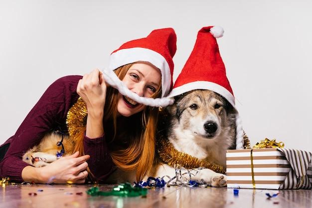 Felice ragazza dai capelli rossi con un berretto rosso come babbo natale si siede sul pavimento con il suo cane, atmosfera di capodanno