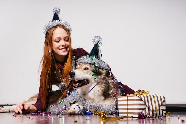 Felice ragazza dai capelli rossi con un berretto in testa si siede sul pavimento con il suo cane che celebra il nuovo anno 2018