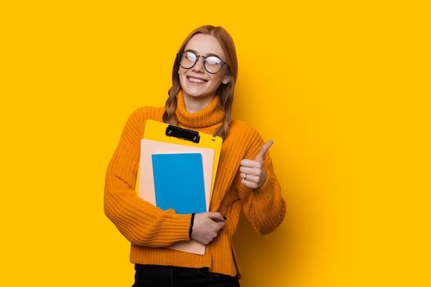 Felice studente dai capelli rossi con le lentiggini e gli occhiali è in possesso di alcuni libri e gesticola il segno simile