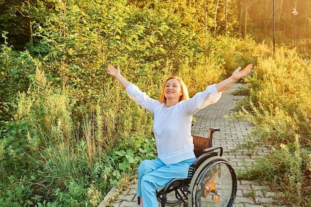 Felice donna dai capelli rossi in sedia a rotelle godendo di tempo soleggiato alzando le mani. giornata internazionale delle persone con disabilità