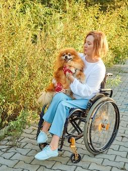 Felice donna dai capelli rossi su una sedia a rotelle per una passeggiata con il suo cane. giornata internazionale delle persone con disabilità