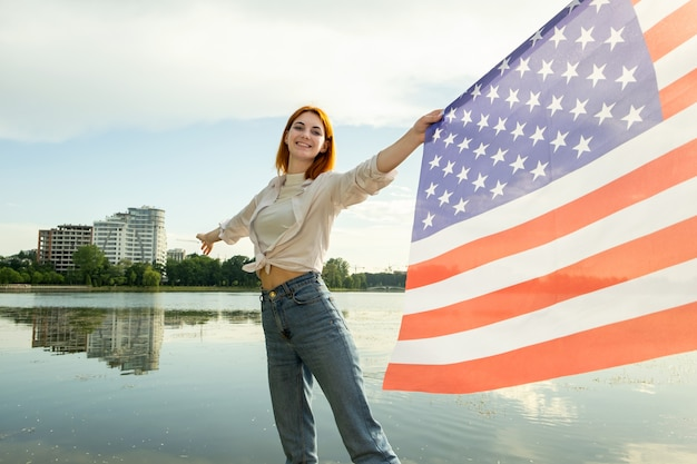 Giovane donna dai capelli rossi felice con la bandiera nazionale degli stati uniti in sua mano. ragazza positiva che celebra la festa dell'indipendenza degli stati uniti.