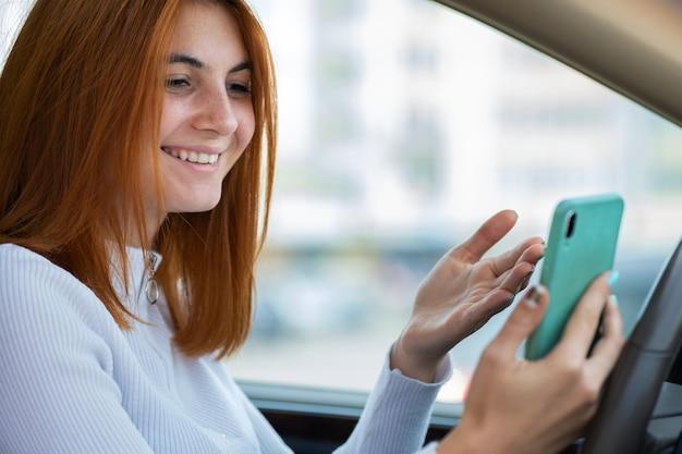 Ragazza felice della testarossa che manda un sms sul suo telefono cellulare dietro la ruota che conduce un'automobile. Foto Premium