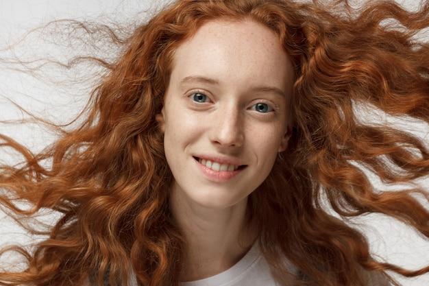 Felice ragazza rossa con i capelli ricci che ondeggia in un torrente d'aria