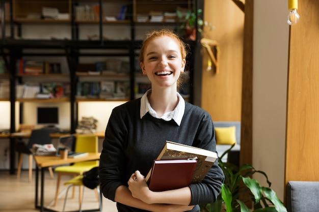Studente di redhead felice che propone all'interno in biblioteca che tiene i libri