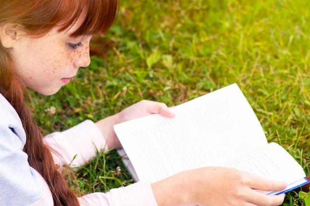 Contento. rossa con le lentiggini, ragazza adolescente, leggendo un libro sull'erba. la femmina sorride, si allena con un libro di testo nel parco. copia spazio