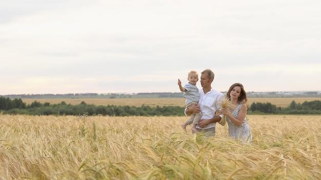 Relazione felice, giovane famiglia che cammina insieme su un campo di grano. madre, padre e figlio piccolo svaghi insieme all'aperto. genitori e bambino che giocano sul prato estivo