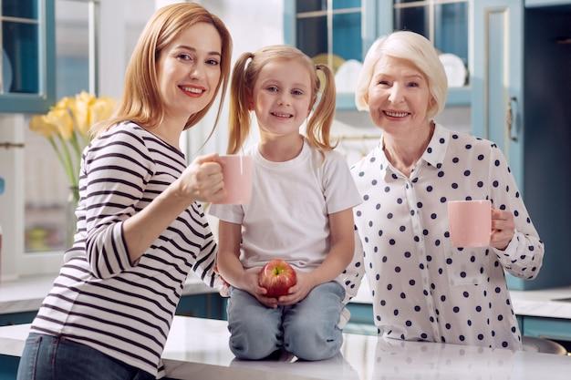 Parenti felici. adorabile bambina seduta sul bancone della cucina e che tiene una mela mentre sua madre e nonna allegre stanno al suo fianco e tengono le tazze di caffè