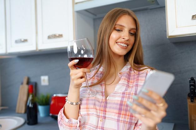 Felice giovane donna rilassata in piedi in cucina con un bicchiere di vino rosso e utilizzando il suo smartphone