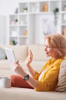 Donna matura riposante felice in abbigliamento casual rilassante sul divano mentre beve il tè e comunica tramite chat video in tablet a casa