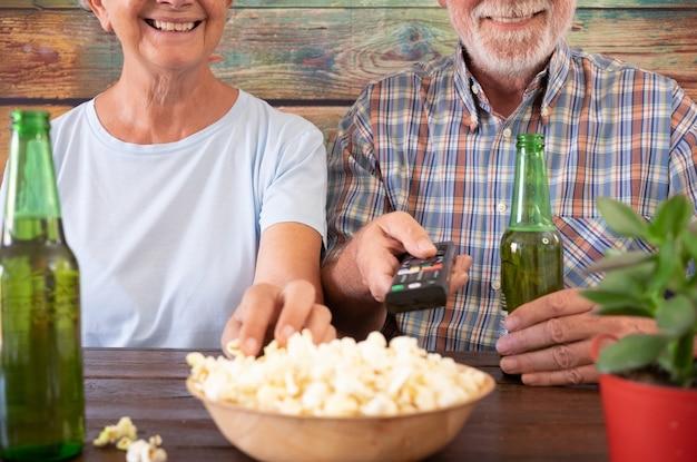 Felice coppia in pensione guardando la partita di calcio seduto al pub con due bottiglie di birra e un po' di popcorn. due anziani attraenti