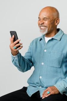 Uomo in pensione felice che utilizza uno smartphone