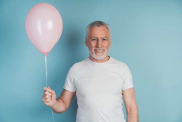 Uomo in pensione felice in maglietta bianca che tiene palloncino rosa mentre posa in studio.