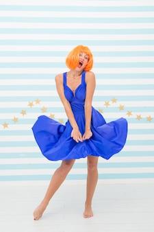 La donna retrò felice con un aspetto pazzo tiene il vestito ventoso. ragazza pazza con la faccia felice e i capelli arancioni. pin up girl in abito retrò dicendo oops alla gonna ventosa. vintage alla moda e sexy. bellezza e moda.
