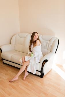 Felice ricca giovane donna indossa abito da notte in un moderno hotel di casa, buongiorno concetto di lifestyle