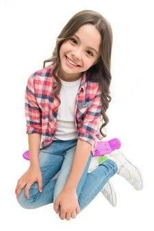 Buon viaggio. la ragazza del bambino felice si siede a bordo del penny. originariamente progettato come skateboard per ragazze. hobby adolescente moderno. la faccia felice della ragazza si siede sul fondo bianco del bordo del penny. imparare a guidare penny board.