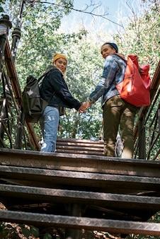 Felice coppia romantica di turisti stanno salendo sui gradini vista posteriore