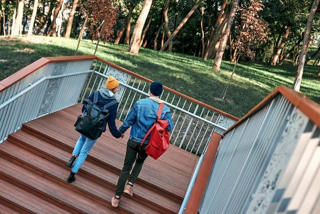 Felice coppia romantica di turisti si tengono per mano sulla vista posteriore dei gradini