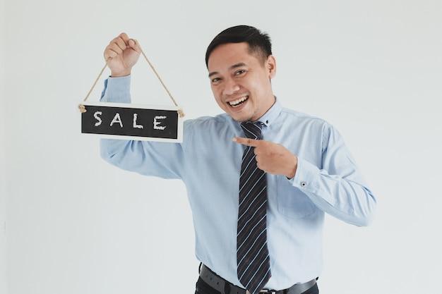 Felice addetto alle vendite che indossa camicia blu e cravatta in posa con l'indicazione e il trasporto del cartello vendita su sfondo bianco