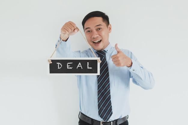 Felice addetto alle vendite che indossa camicia blu e cravatta in posa con il pollice in alto e porta il cartello deal alla telecamera su sfondo bianco
