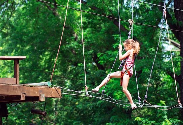Ragazza felice della scuola che gode dell'attività in un parco di avventura di arrampicata in una giornata estiva,