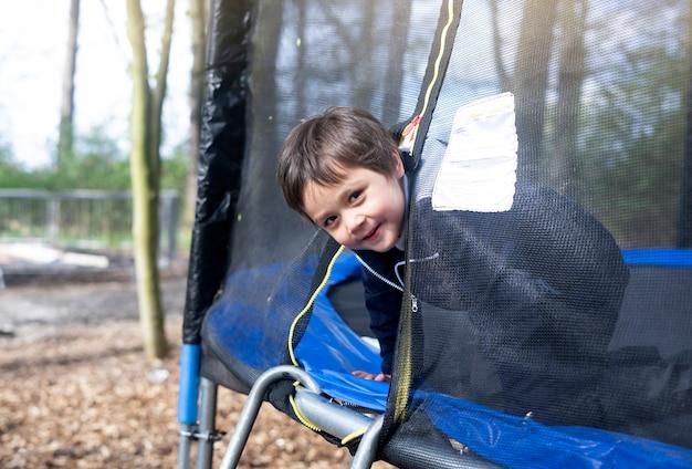 Bambino felice della scuola che si arrampica nel lato del trampolino