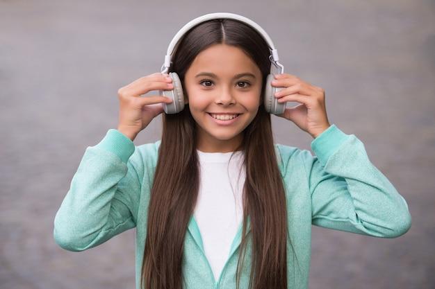 Il ragazzo felice della scuola ascolta musica o audiolibro in cuffia per l'educazione e la gioia, l'infanzia.