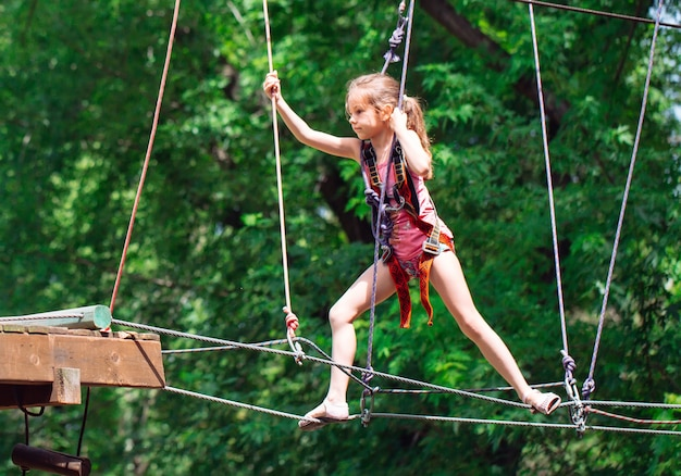Donna felice della scuola che gode dell'attività in un parco di avventura di arrampicata in una giornata estiva,