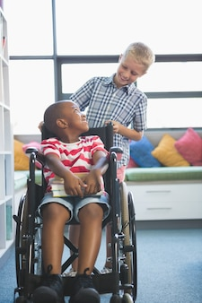 Scolaro felice che trasporta il suo amico in sedia a rotelle