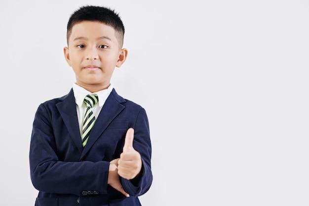 Scolaro felice in uniforme scolastica che mostra il pollice in su, isolato su bianco
